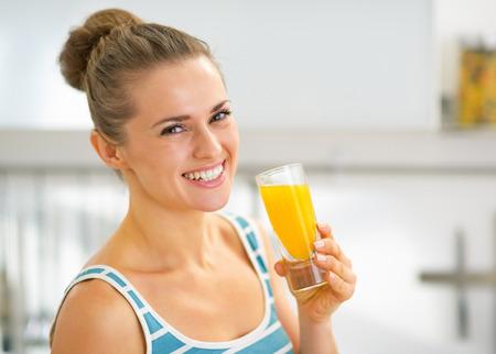 신선한 오렌지 주스의 유리와 웃는 젊은 여자의 초상화