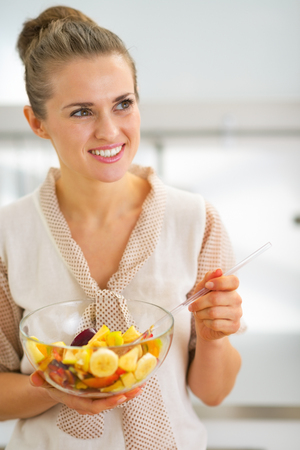 Portrait of happy young housewife mixing fruit salad photo