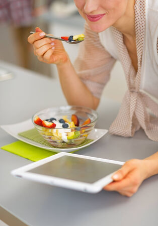topicality: Closeup on happy young woman eating fruit salad and using tablet pc Stock Photo