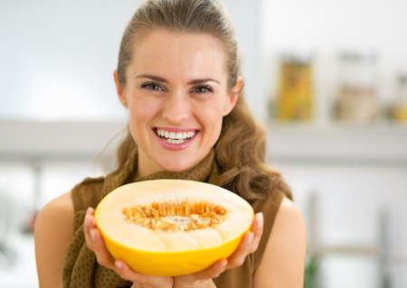 Happy young woman showing melon slice photo