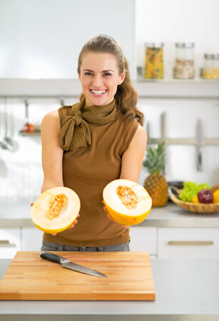 Smiling young woman showing melon slices in kitchen photo