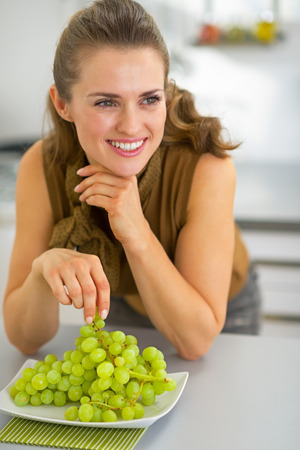 Happy young woman eating grape in kitchen Stock Photo - 31040801