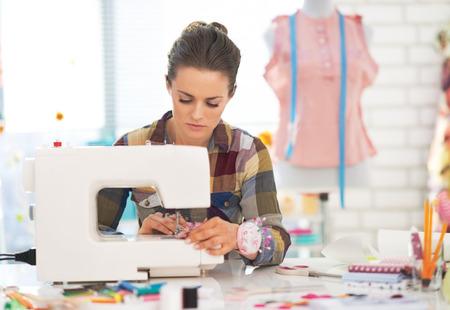 máquina de coser: Mujer modista que trabaja con la máquina de coser Foto de archivo