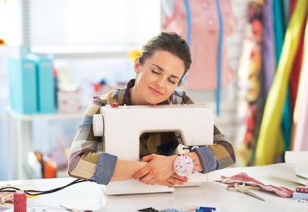 Gelukkig kleermaker vrouw knuffelen naaimachine Stockfoto
