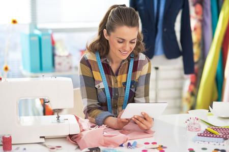 maquinas de coser: Mujer sastre feliz con tablet pc en el trabajo Foto de archivo