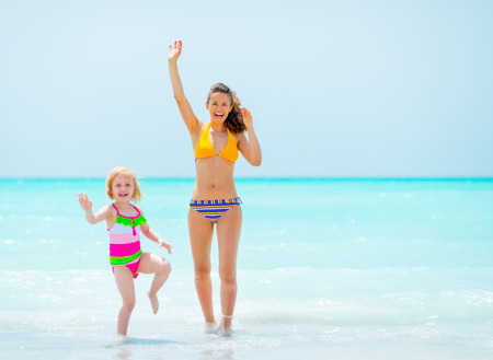 Mother and baby girl waving with hand on sea coast photo