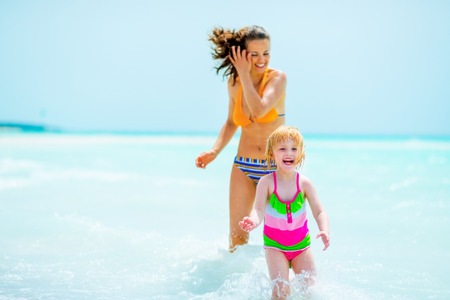 Happy mother and baby girl playing on sea shore photo