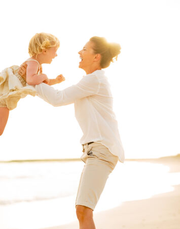Mother and baby girl playing on the beach in the evening photo