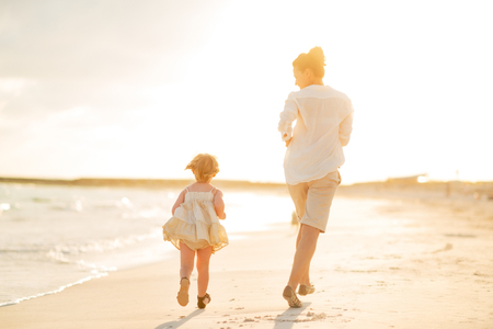to hasten: Mother and baby girl running on the beach in the evening. rear view