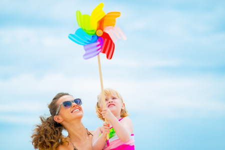 molino: Feliz madre y el bebé que sostiene el molino de viento de juguete de colores