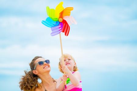 Gelukkige moeder en baby meisje bedrijf kleurrijke windmolen speelgoed
