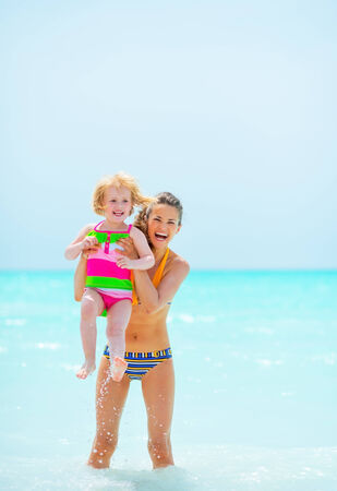 Portrait of mother and baby girl in sea photo