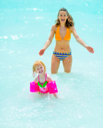Portrait of mother and baby girl playing in sea photo