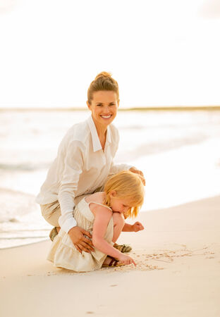 Happy mother and baby girl playing on the beach in the evening photo