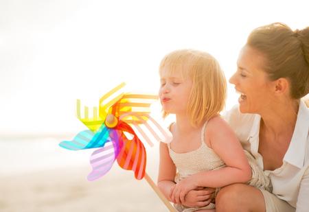 Moeder en baby meisje spelen met kleurrijke speelgoed windmolen op het strand in de avond Stockfoto