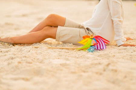 Closeup on young woman sitting on the beach in the evening with colorful windmill toy photo