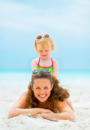 Portrait of smiling mother and baby girl playing on beach photo