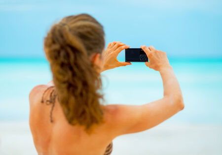 Young woman taking photo on beach. rear view