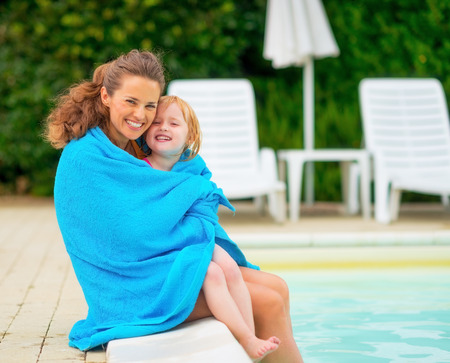 Portrait of happy mother and baby girl wrapped in towel sitting near swimming pool photo