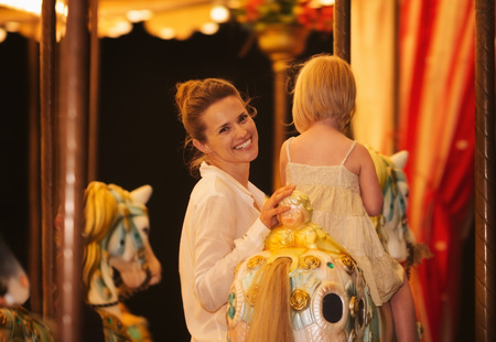 Mother and baby girl riding on carousel photo