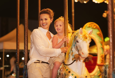 Happy mother and baby girl riding on carousel photo