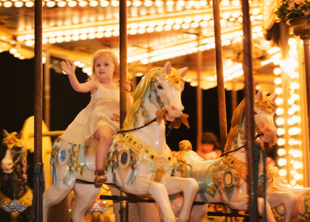 Portrait of happy baby girl riding on carousel photo