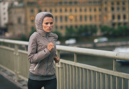 Fitness young woman jogging in rainy city