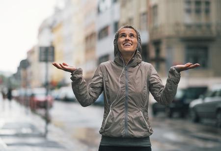 Gelukkige geschiktheids jonge vrouw die regendalingen in de stad vangt