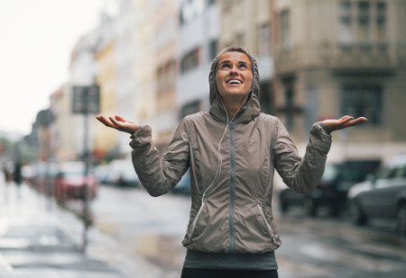 Happy fitness young woman catching rain drops in the city Фото со стока