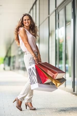 Volledige lengte portret van lachende jonge vrouw met boodschappentassen op het winkelcentrum steegje