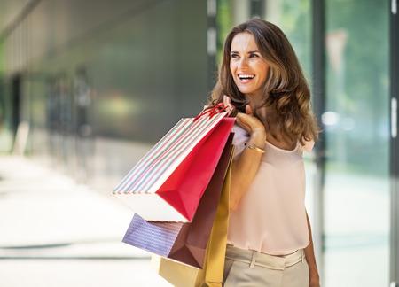 Gelukkige jonge vrouw met het winkelen zakken op de wandelgalerijsteeg die op exemplaarruimte kijken