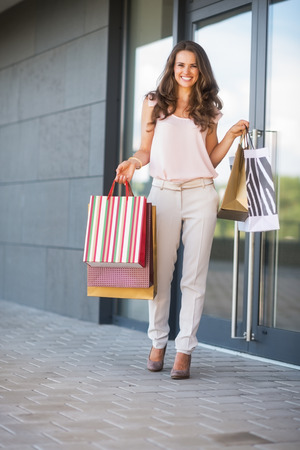 Full length portrait of happy young woman with shopping bags near shop door photo