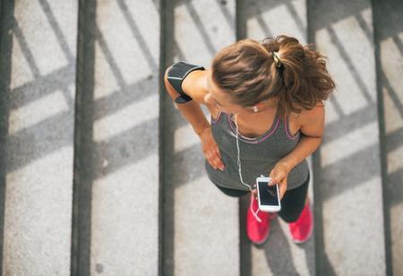 Portré fitness fiatal nő mobiltelefonján a szabadban, a város
