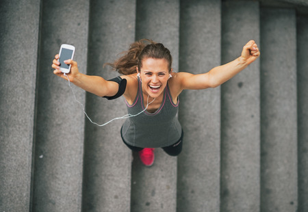 women exercise: Portrait of happy fitness young woman with cell phone outdoors in the city rejoicing