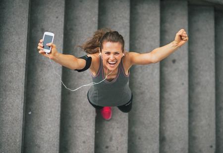 Portret van gelukkige fitness jonge vrouw met een mobiele telefoon buiten in de stad verheuging