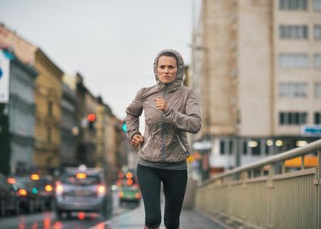 Fitness jonge vrouw joggen in regenachtige stad Stockfoto