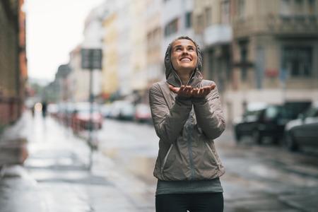 Boldog fitness fiatal nő gyönyörködtető eső esik a város Stock fotó
