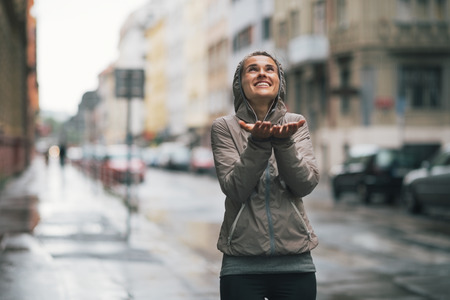 Happy fitness young woman catching rain drops in the city Stok Fotoğraf