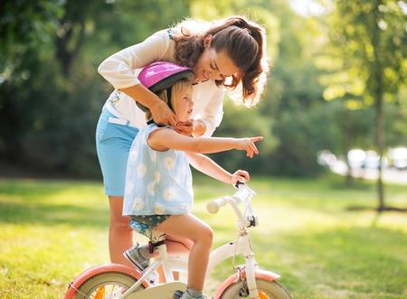 Moeder dragen van helm op baby meisje op de fiets