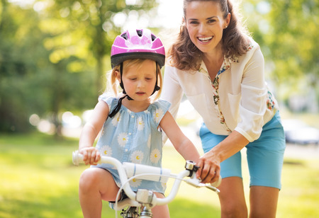 mother helping baby: Happy mother helping baby girl riding on bicycle