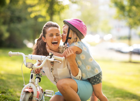 Happy mother and baby girl having fun in park with bicycle Stockfoto