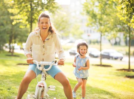 Moeder en baby meisje met plezier met de fiets in het park
