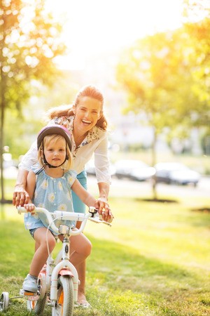 Portrait of happy mother helping baby girl riding bicycle in park Stock Photo