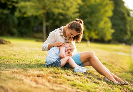 outdoor  outside: Mother and baby girl sitting outdoors in the evening