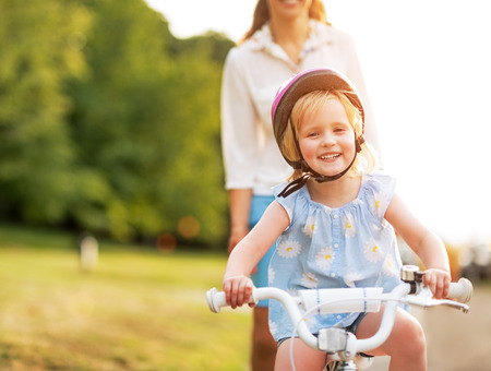 Smiling baby girl riding bicycle Stock Photo