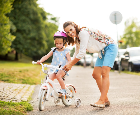nature protection: Mother helping baby girl riding bicycle Stock Photo