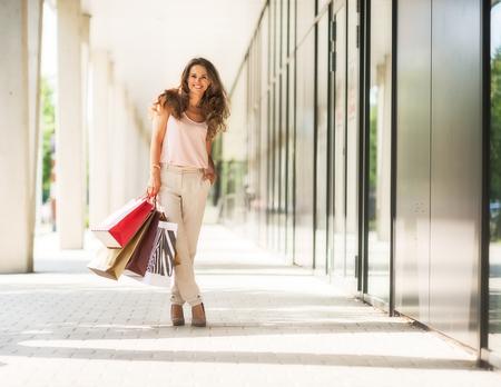 쇼핑몰 골목에 쇼핑 가방과 함께 행복 한 젊은 여자의 전체 길이 초상화