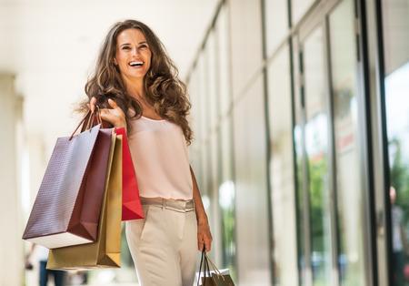 Portret van gelukkige jonge vrouw met boodschappentassen op het winkelcentrum steegje