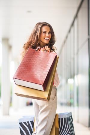 Portré, boldog fiatal nő, bevásárló táskák Stock fotó