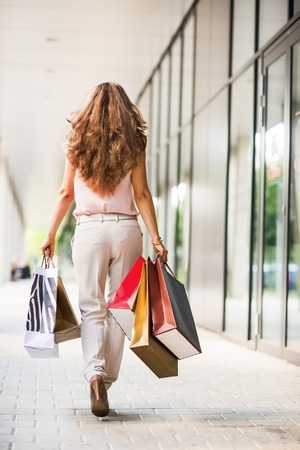 go shopping: Young woman with shopping bags walking on the mall alley. rear view Stock Photo